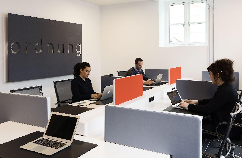 To kvinder og en mand der arbejder fra hver deres kontorplads