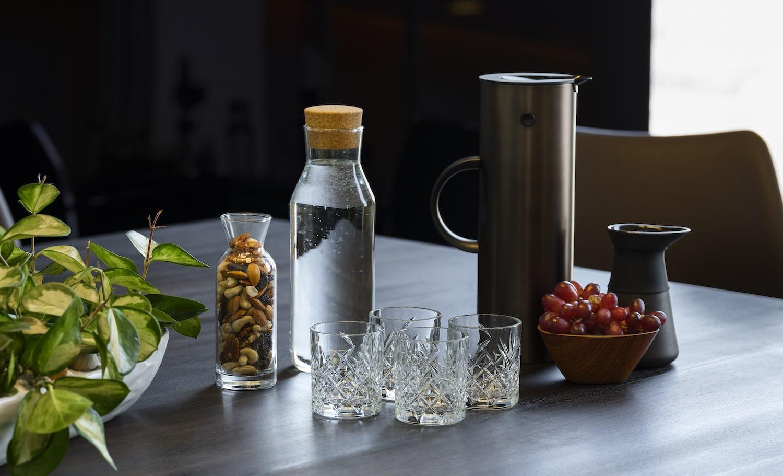 Mødeforplejning bestående af glas med nødder, vandglas og vandkaraffel, kaffekande, mælkekande og en skål med røde vindruer