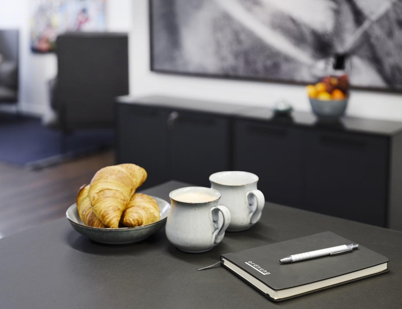 Kaffekopper, croissanter, notesbog og kuglepen på sort bord