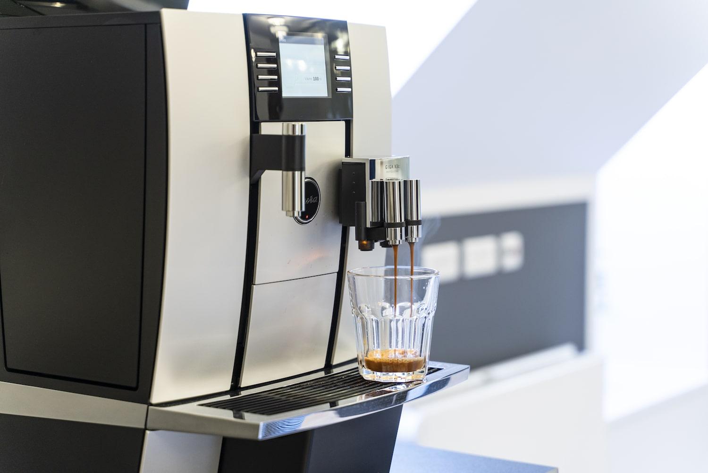 Kaffemaskinen brygger en kop kaffe