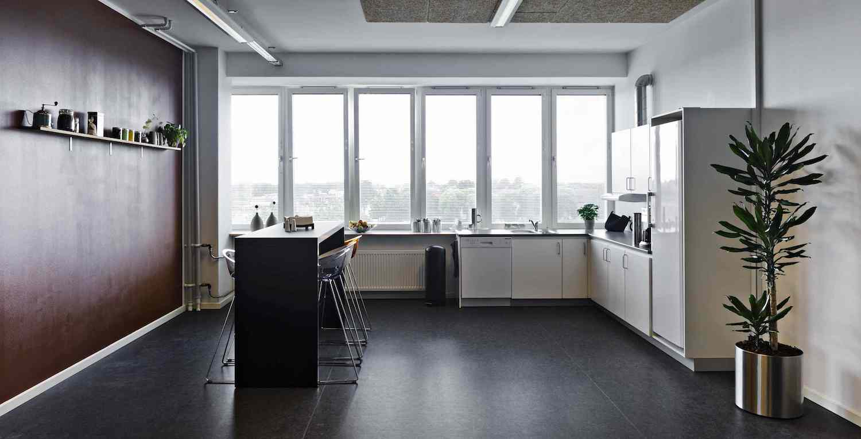Rummeligt køkken med højbord og barstole