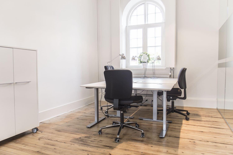 Møbleret kontor i lyst hvidmalet lokale