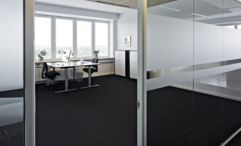 Et kig ind ad døren til det store møbleret kontor med udsigt over København