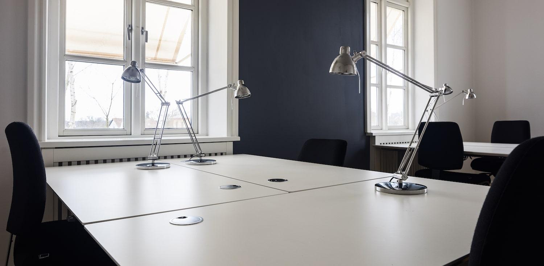 Kontorpladser bestående af hvide skriveborde, sort kontorstole og sølvgrå lamper
