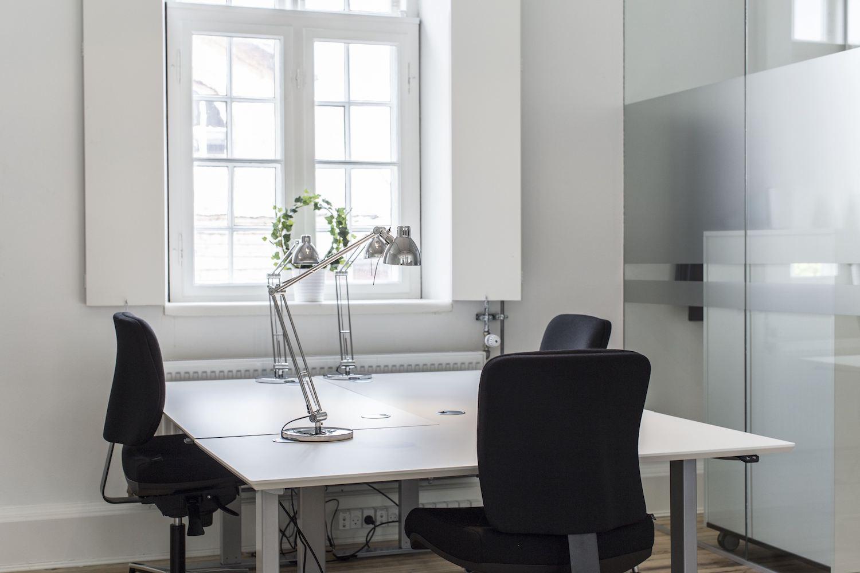 Møblerede kontorpladser foran vindue