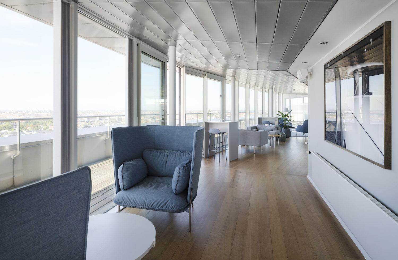 Gangareal i loungeområde med bløde møbler langs vinduerne