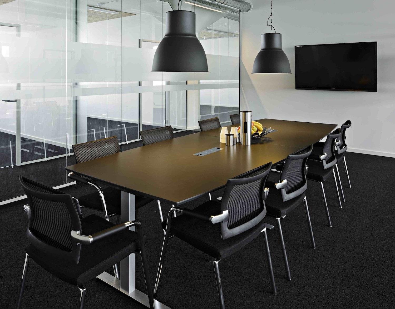 Stort mødelokale med sort møblement og let forplejning