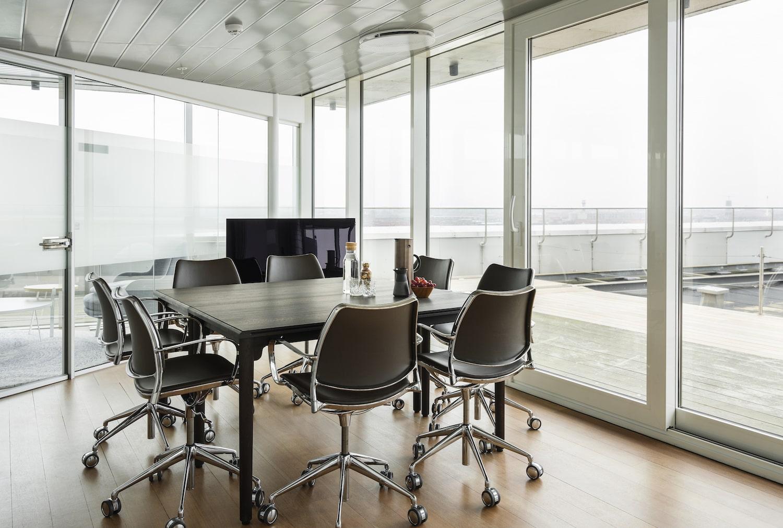 8 kontorstole rundt om det mørke mødebord, hvorpå der står kaffe, vand, nødder og vindruer
