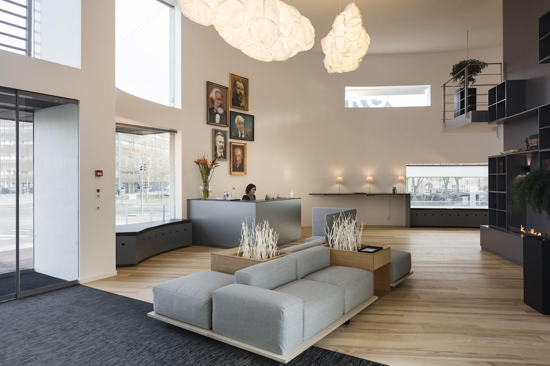 Receptionsområde med loungesofa, reception og bagvedhængende portrætter