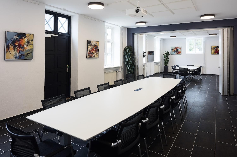 Rummeligt mødelokale med sprossede vinduer