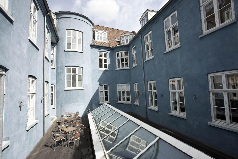 Tagterrasse omgivet af den blå bygning