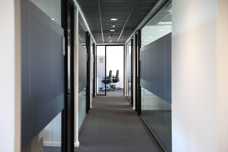 Gangareal med glasvægge der leder til kontorerne