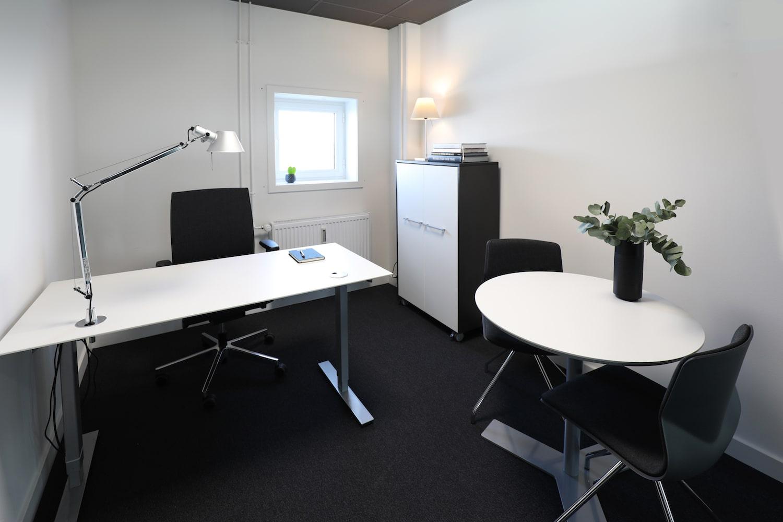 Lyst enkeltmandskontor med lille mødebord