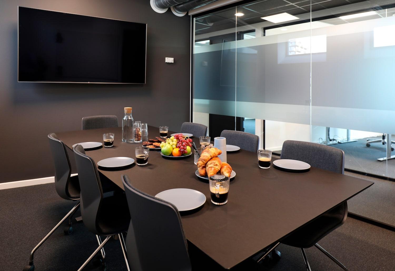 Opdækket mødelokale med omfattende forplejning